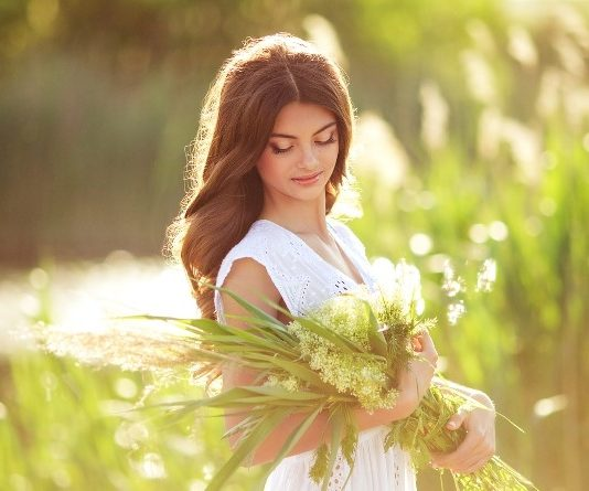 Beautiful woman in a white dress in a field, gathering herbs for her skin care regimen, including skin firming and wrinkle removing creams.